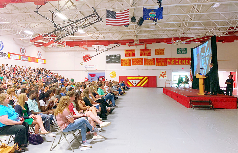 Dr. Bob Ballard speaking to a gymnasium of high school students about his expedition to the remote Pacific in an effort to discover Amelia Earhart's missing airplane.