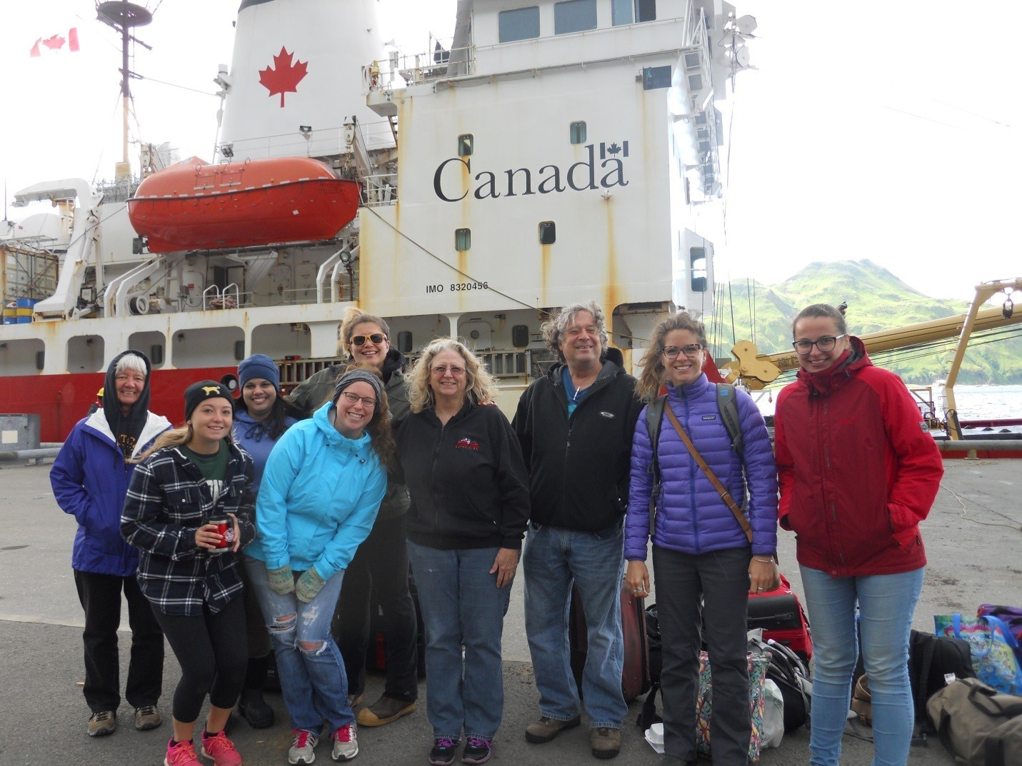 Student Sophie Caradine-Taber standing with researchers at dockside in front of the Sir Wilfrid Laurier icebreaker