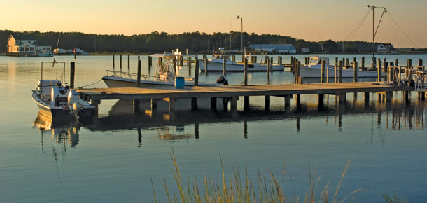 boats along dock on water at sunset