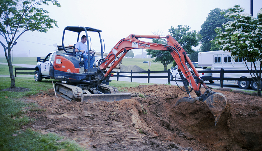 piece of construction equipment being used to dig a large hole for a rain garden