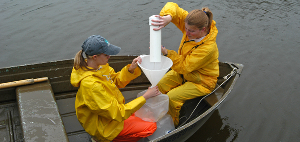 graduate students taking samples in small boat