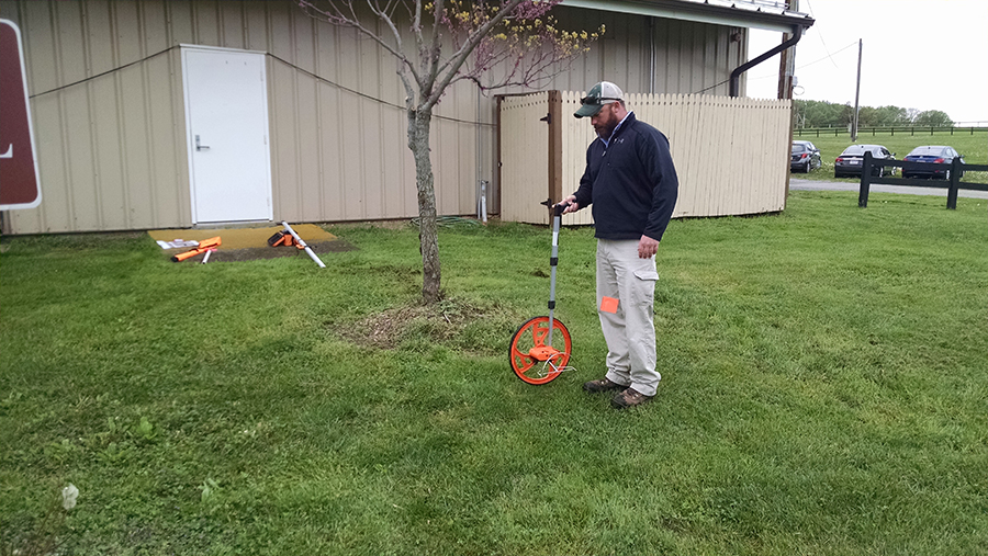 man uses wheel-like device to measure out length of a new rain garden