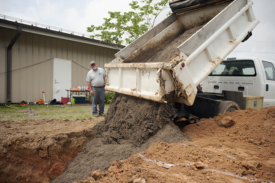 dump truck dumping soil into a hole in the ground for rain garden