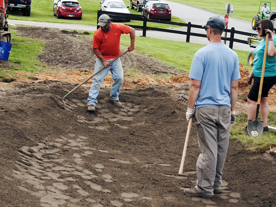 several people using garden rakes to shape the contours of topsoil for a rain graden