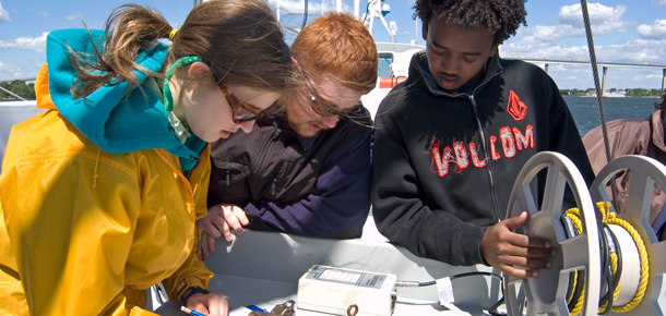 students on research boat taking measurements