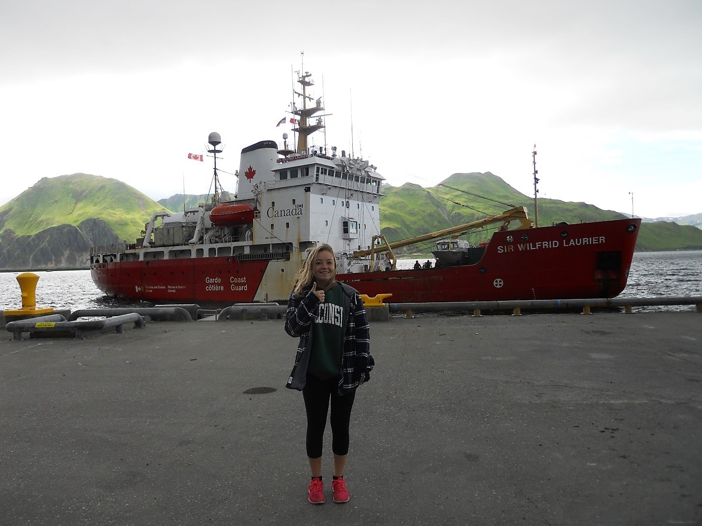 photo of student Sophie Caradine-Tauber standing at dockside in front of the Sir Wilfrid Laurier icebreaker