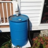 image of rain barrel conencted to home downspout