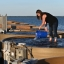 Shannon Hood holds pours water from a blue bucket while standing in an oyster tank