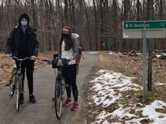 Carly Maas and a fellow student take their bikes to a research site in Rock Creek.