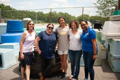 Five attendees posing in front of tanks used for aquaculture systems.