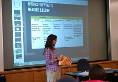 Jennifer Dindinger stands in front of a screen showing a presentation slide titled Options for What to Measure & Report