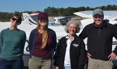 Cora Johnston, Julia Rentsch, Mary MacMutcheon, and Scott Lerberg in front of airplane