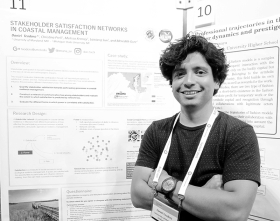 Daniel Teodoro with his poster on the importance of stakeholder satisfaction at a conference in The Netherlands.