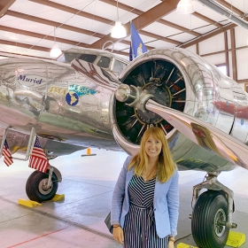 Melanie Jackson standing in front of Muriel, one of only 14 Lockheed Electra L-10E airplanes ever made—in 1935—and the last surviving one.